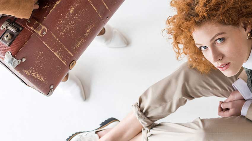 Woman with frizzy, curly, red hair, sitting next to her suitcase.