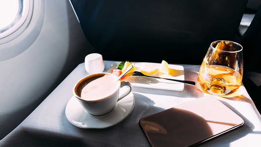 A glass of whisky and a coffee on an aircraft seat tray.